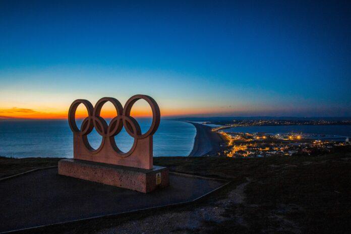 Eine Skulptur der Olympischen Ringe, dahinter eine Küstenstadt bei Nacht