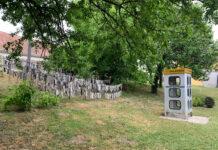 Handytelefonzelle mit Sockenskulptur im Außenbereich des Nonseums