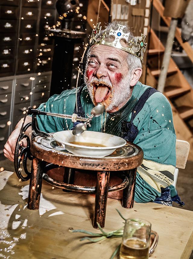 Nonsens-Erfindung: Ein Mann lässt sich von einer Vorrichtung Suppe in den Mund löffeln.