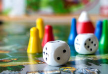 Würfel und Spielfiguren auf einem Spielbrett